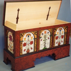 """This decorated pine Blanket Chest was crafted to be auctioned at a """"Chair-ity"""" fundraiser for the Ann Arbor, Michigan Hospice. As I recall it was about 52 inches in length. The pine wood body is faux-painted, and the floral panel designs are derived from a number of sources, but primarily inspired by those motifs used by Pennsylvania Dutch."""
