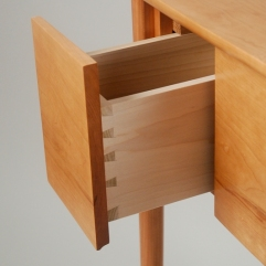 A joinery detail of the poplar drawer side. You open the drawer by pulling on the lip milled into the bottom of the cherry drawer front.
