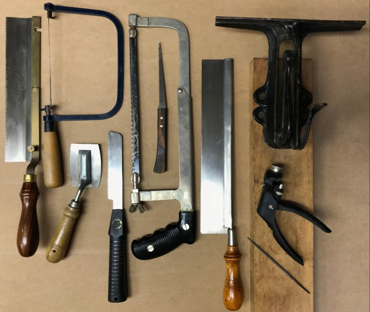 an assortment of hand saws and sharpening devices