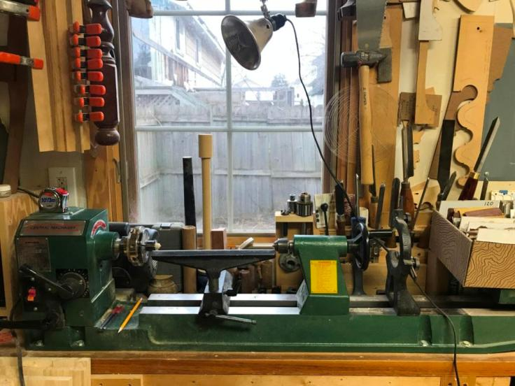 A woodowrking Lathe with accessories including a steady rest and a four-jaw chuck