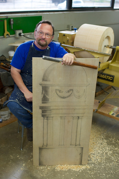 man holding a wood turning gouge and a large pencil drawing on plywood of an architectural cupola. Man is sitting in front of large wood lathe.