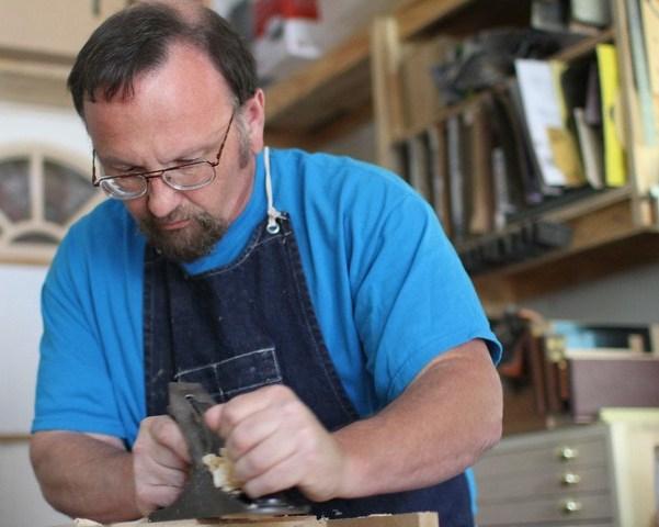 man using metal plane to smooth wood surface