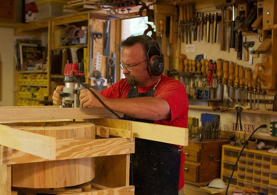 man using woodworking router to surface end grain of object