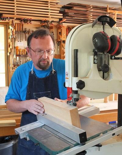 man using bandsaw to cut wood