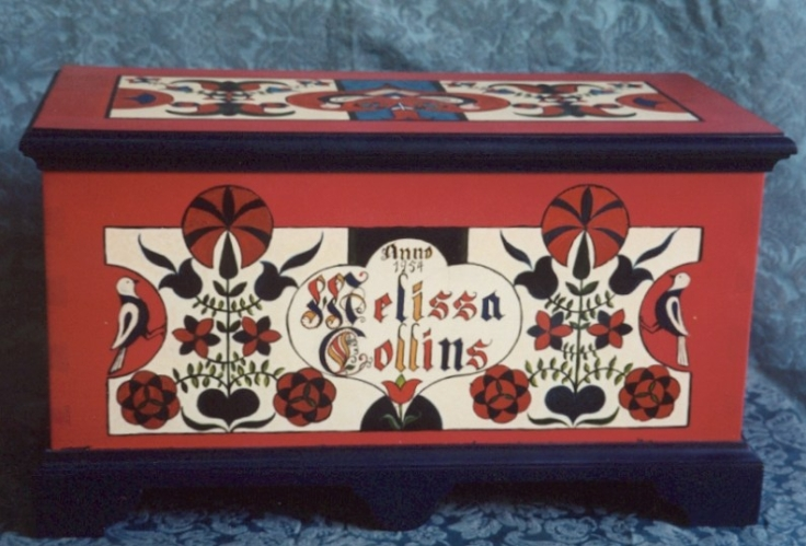 A small red chest with blue trim and painted decorations of birds flowers and hearts