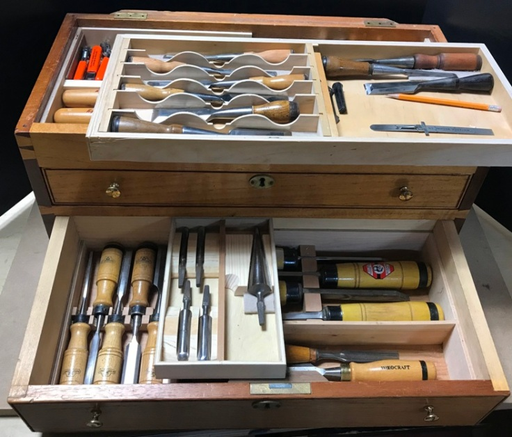 A mahogany tool chest with bottom drawer pulled open displaying contents